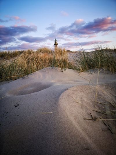 Road leading towards lighthouse on field against sky