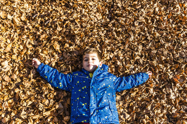 Kid lying on a leaves ground Montseny Autumn One Person Waist Up Front View Clothing Child Blue Sweater Childhood Directly Above Warm Clothing Portrait Boys Leaf Plant Part Smiling Casual Clothing Standing Human Arm Innocence Hands Behind Head Arms Raised Outdoors Scarf