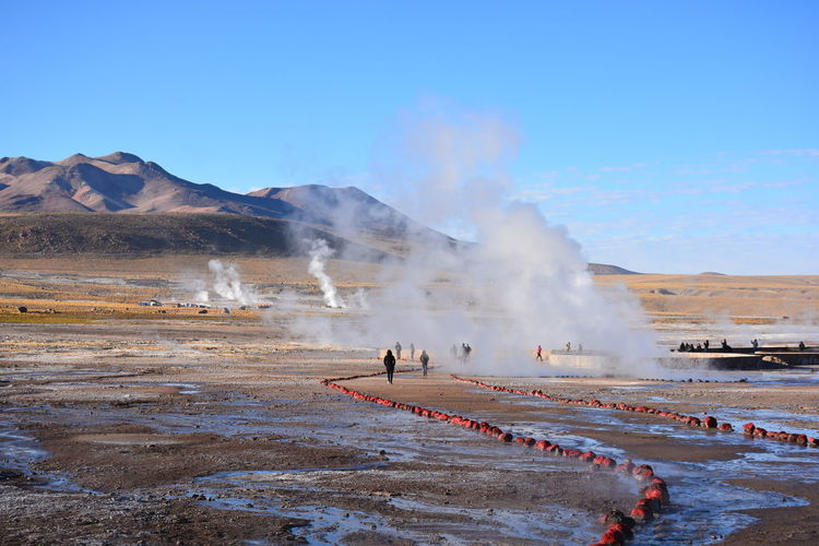 People at hot spring against mountain