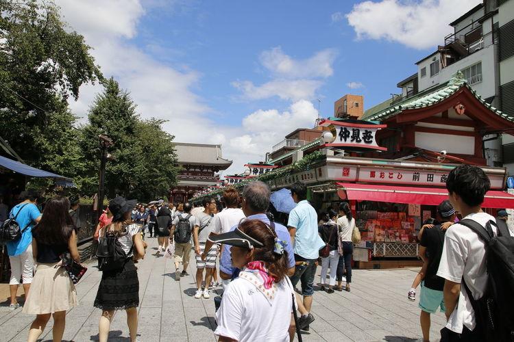 People on sidewalk against sky
