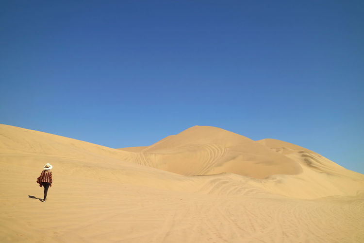 Rear view of woman walking on sand at desert against sky