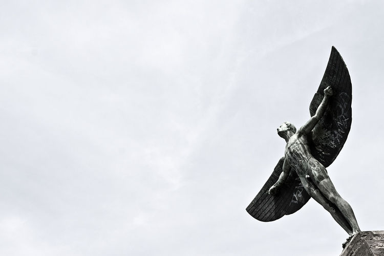 Winged Human Statue Against Clear Sky