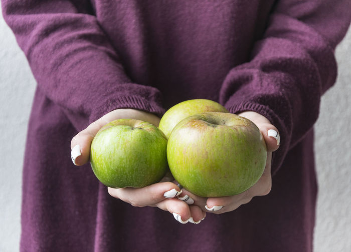 Midsection Of Woman Holding Green Apples