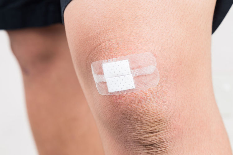 Closeup on person with bandage on the knee limb Asian  Adhesive Bandage Bandage Body Part Close-up Healthcare And Medicine Human Body Part Human Limb Limb One Person Physical Injury Recovery