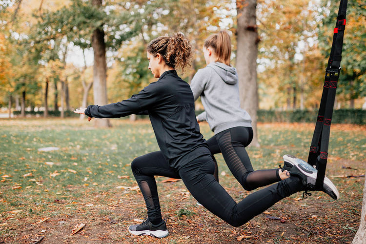 Rear view of women exercising in park