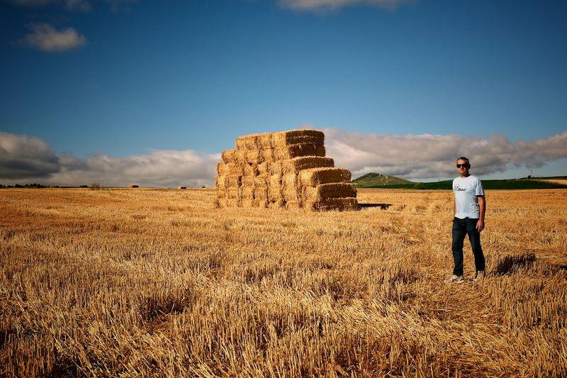 Man Standing On Grassy Field Against Sky