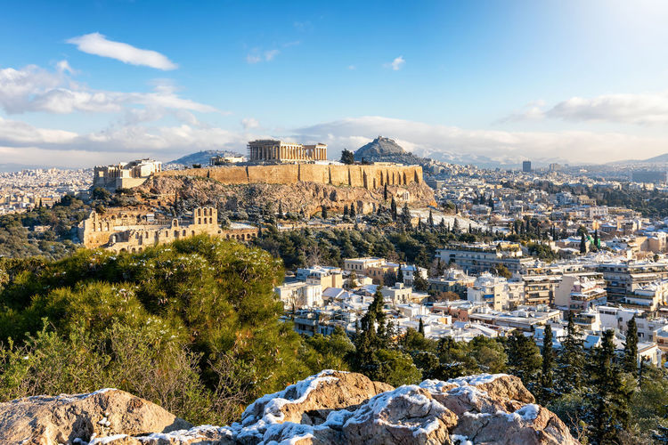 View over the snow covered old town of Athens, Greece, to the Parthenon Temple above at the Acropolis on a sunny winter day Building Exterior Architecture Built Structure Sky City Cityscape Residential District Building History Mountain Travel The Past TOWNSCAPE Rock - Object Travel Destinations Day Athens Greece Greek Parthenon Temple Ruins Ancient Snow Winter