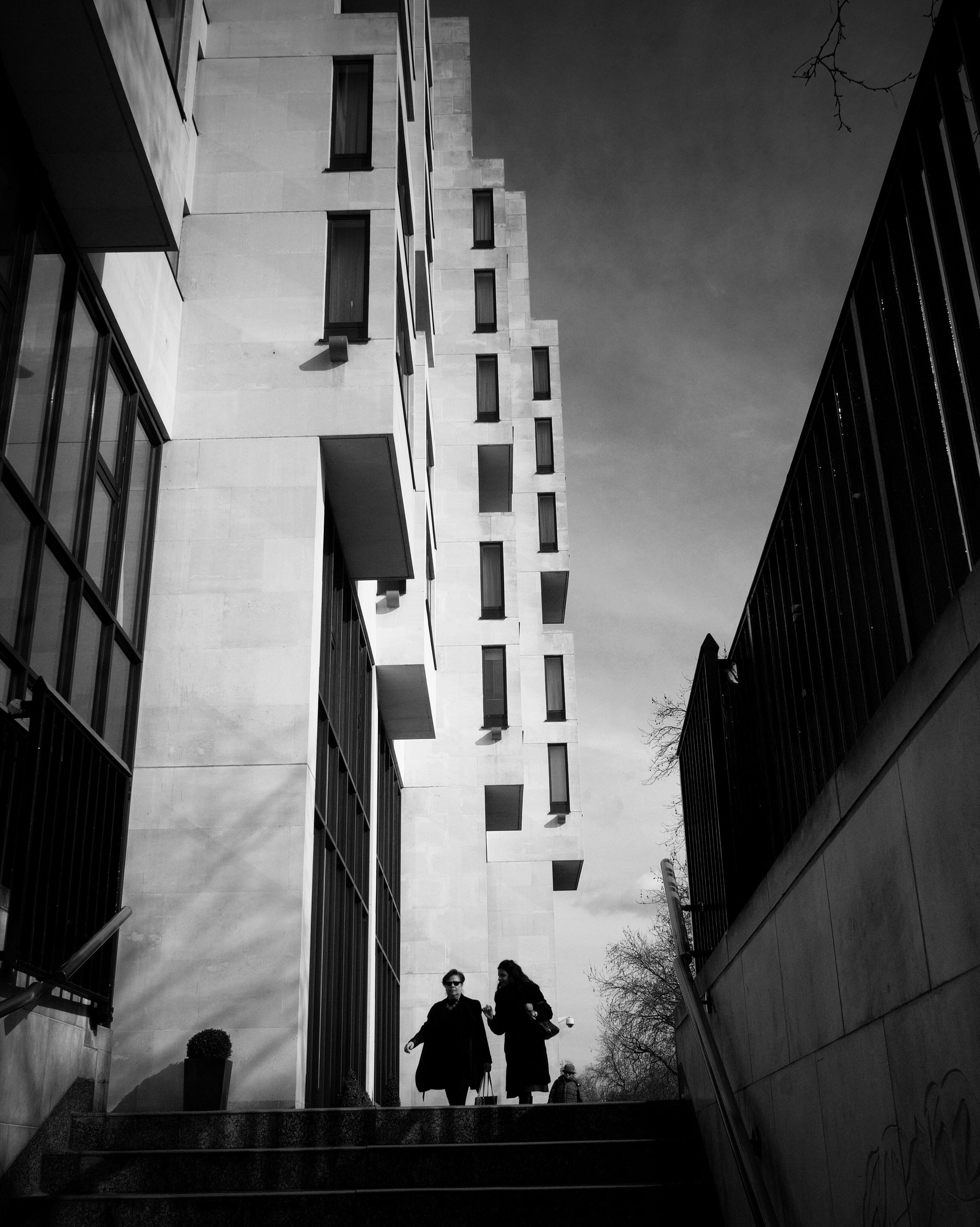architecture, built structure, building exterior, men, walking, building, city, lifestyles, person, low angle view, full length, city life, steps, rear view, leisure activity, railing, modern, residential building