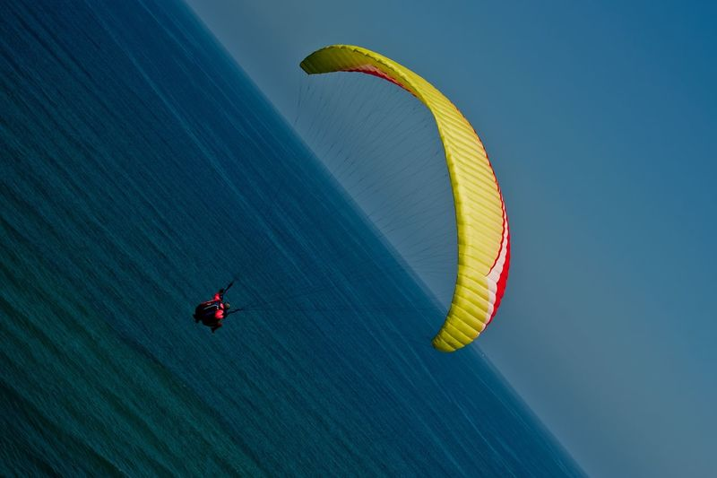 Person paragliding over sea against clear blue sky
