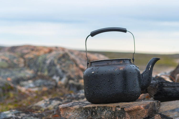 Teapot on stone against sky