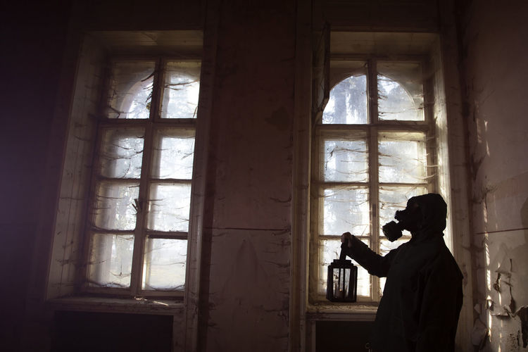 Man photographing through window in building