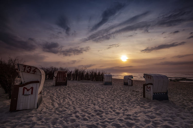 Hooded beach chairs on sand against sky during sunset