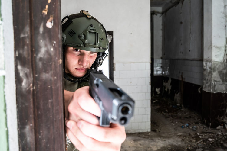 Soldier aiming gun while standing at abandoned building