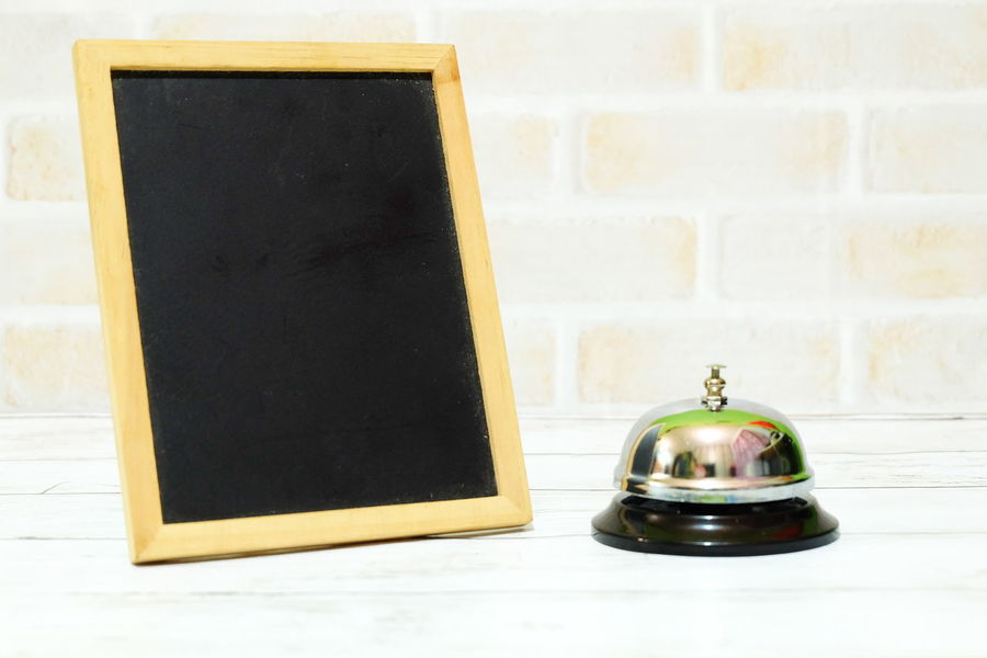 Ring bell and an empty black board. Copy space for text or logo Ring Bell Bell Ring Ting Alarm Sound Hotel Motel Lobby Front Desk Front Counter Office Blackboard  Copy Space Old-fashioned Antique Indoors  No People Close-up Day