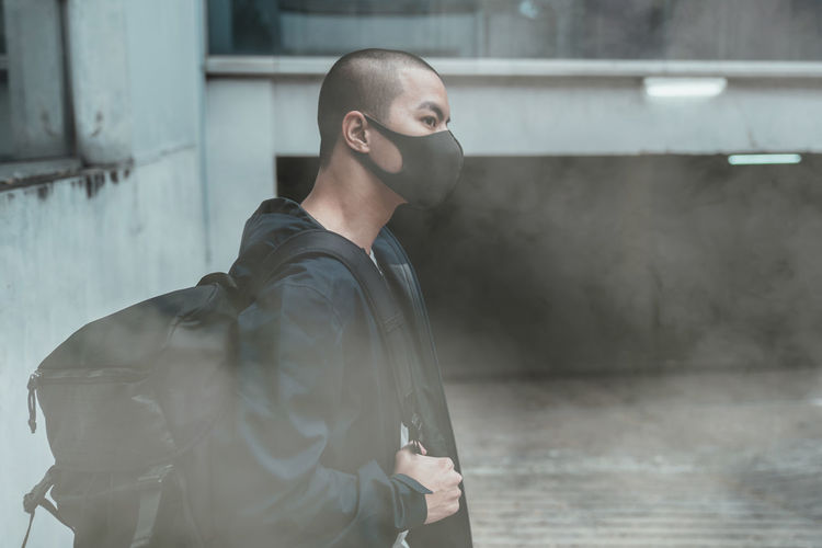 Side view of man wearing mask standing outdoors