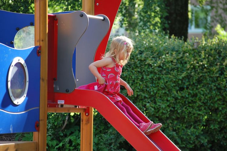 View of girl playing on slide at playground