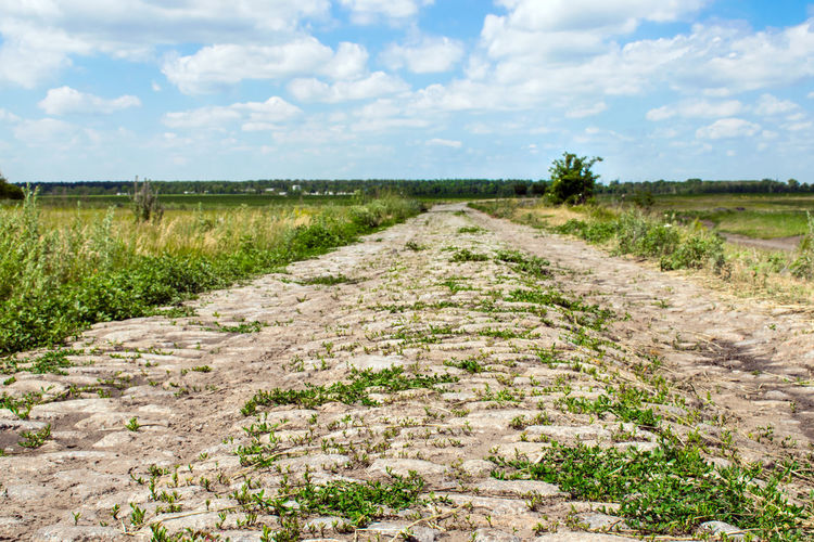 Surface level of dirt road amidst field against sky