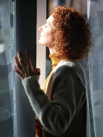Side view of woman with eyes closed sunbathing through window at home