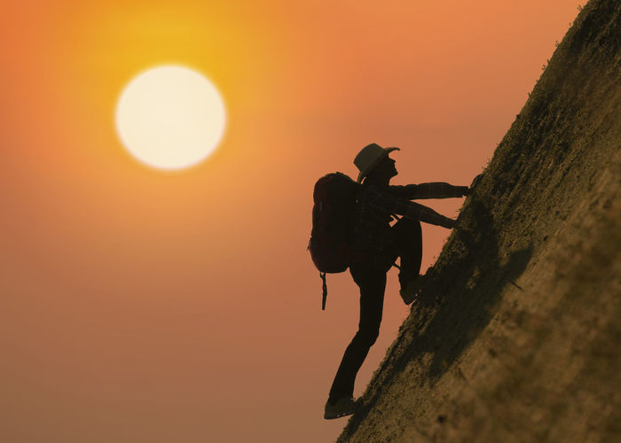 Silhouette of backpacker climbing on mountain at sunset or sunrise Sunset Sky Silhouette Orange Color Activity Lifestyles Climbing Leisure Activity Extreme Sports Real People One Person Nature Sport Adventure Sun Men Beauty In Nature Rock Climbing Outdoors Skill  Effort