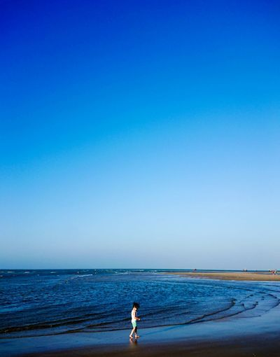 Girl Walking On Beach Against Clear Blue Sky