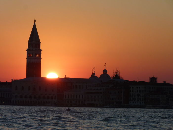 Church of san giorgio maggiore by lake against sky during sunset in city