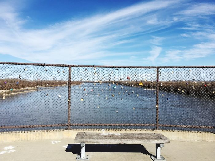Padlocks Attached To Chainlink Fence By Lake