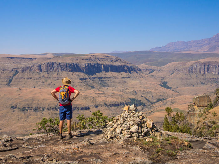 Rear view of man standing on desert against mountain