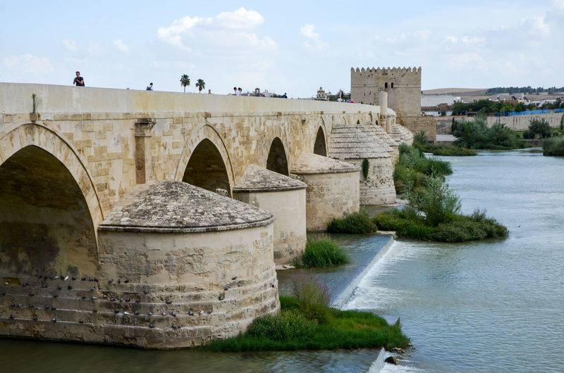 Water Architecture Built Structure Sky Nature History The Past Cloud - Sky Bridge Building Exterior Bridge - Man Made Structure Connection Day River No People Travel Destinations Outdoors Old Arch Arch Bridge Flowing Water Roman Bridge Roman Bridge Córdoba Puente Romano De Cordoba Sightseeing