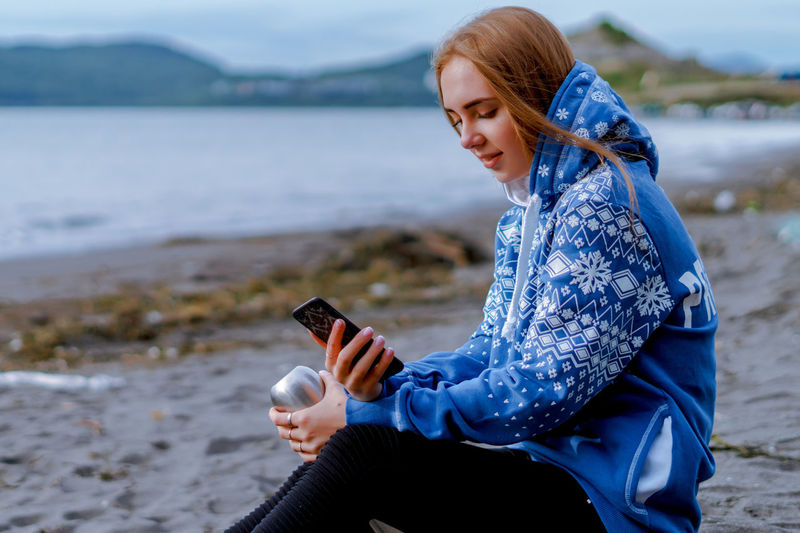Young woman using phone while sitting at beach
