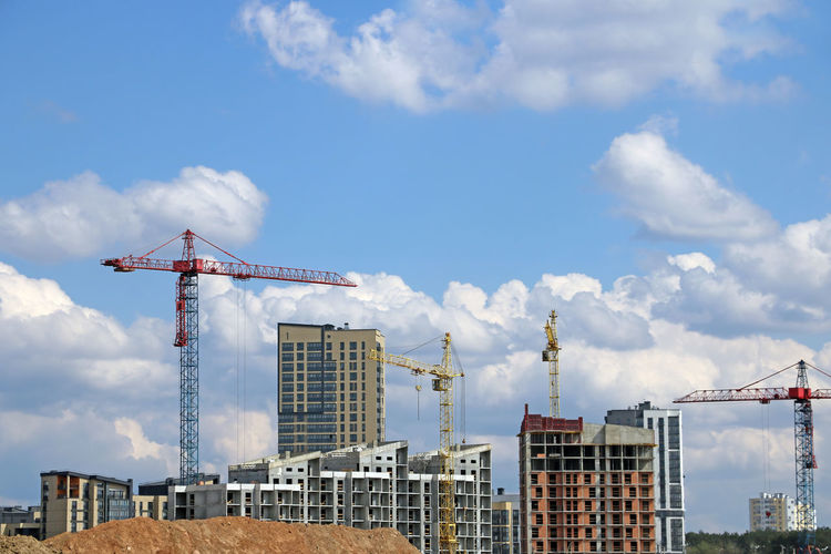 Cranes on construction site against buildings in city