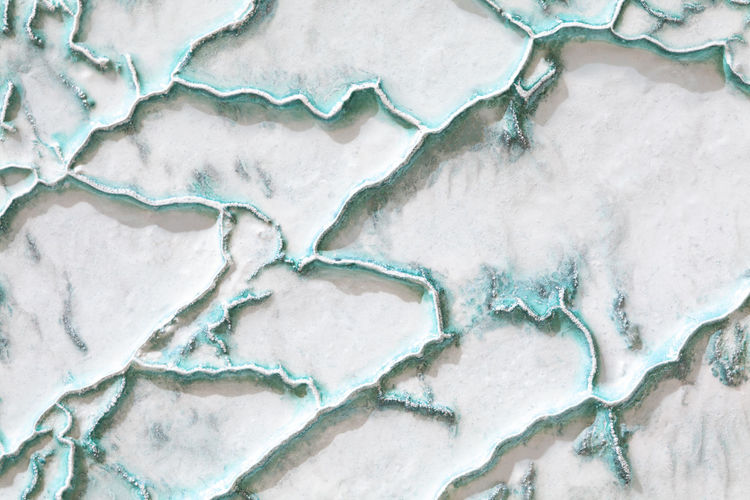 White-turquoise texture of pamukkale calcium travertine in turkey, uneven pattern of big cells