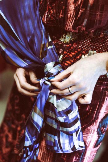 Woman's hand tying silk blue fabric on dress