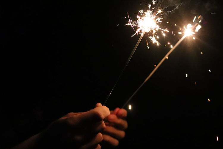 Cropped hands of person holding sparklers at night