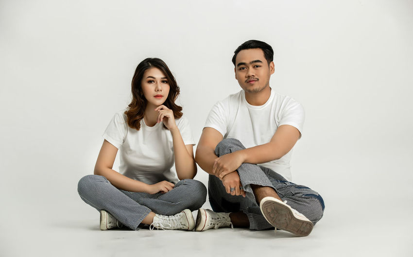 Portrait of young couple sitting against white background