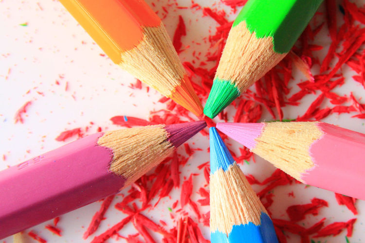 Close-Up Of Colored Pencils With Shaving Over White Background