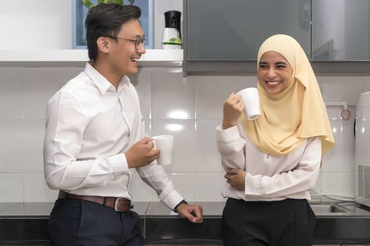 Two young executive malay having a break at pantry Young Adult Three Quarter Length Young Men Smiling Standing Front View Two People Young Women Adult Men Real People Togetherness Happiness Business People Colleague Holding Casual Clothing Indoors  Teamwork Coworker