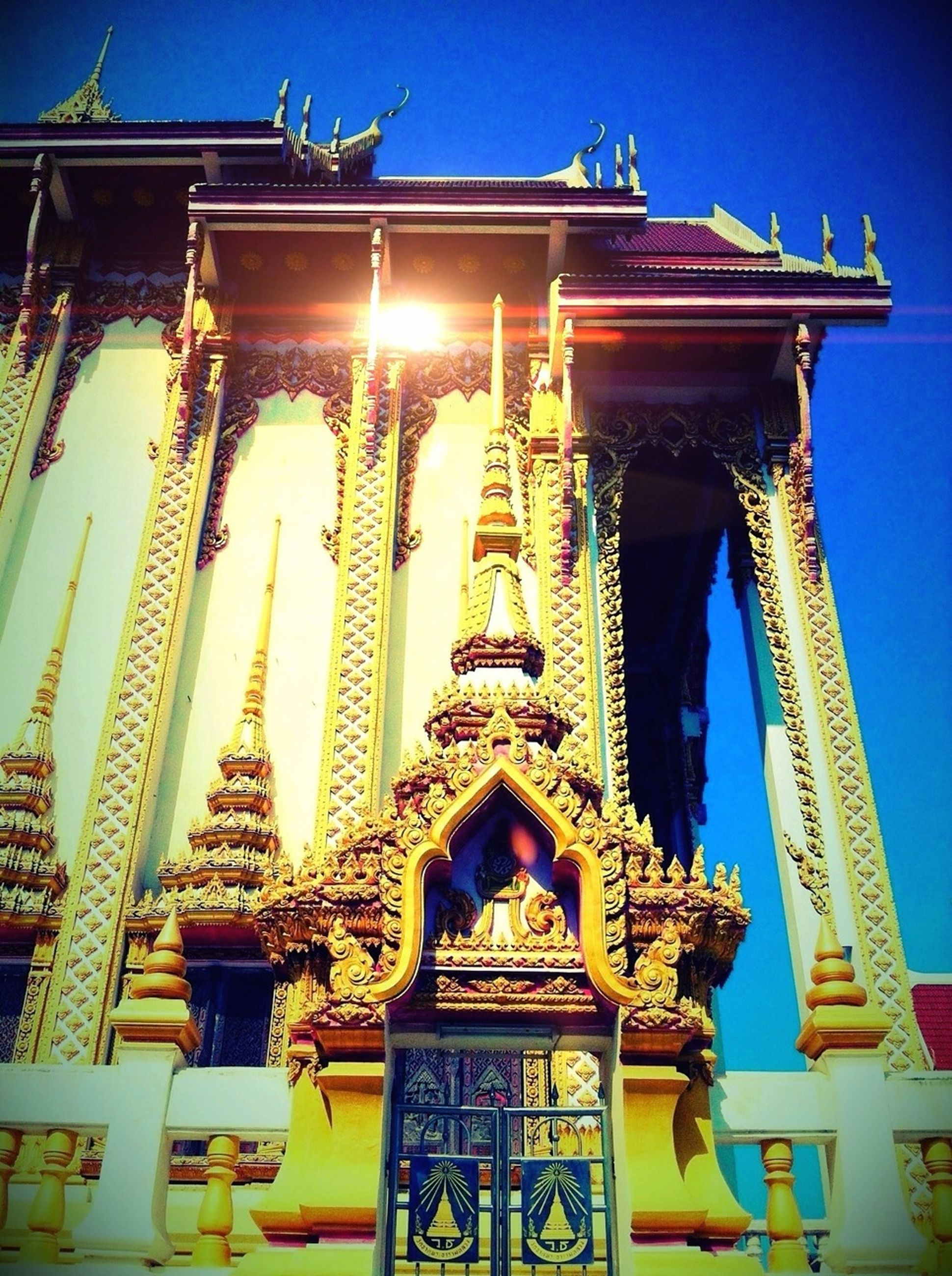 low angle view, architecture, built structure, building exterior, blue, clear sky, sky, sunlight, illuminated, ornate, art and craft, outdoors, religion, no people, spirituality, city, lighting equipment, art, place of worship, day