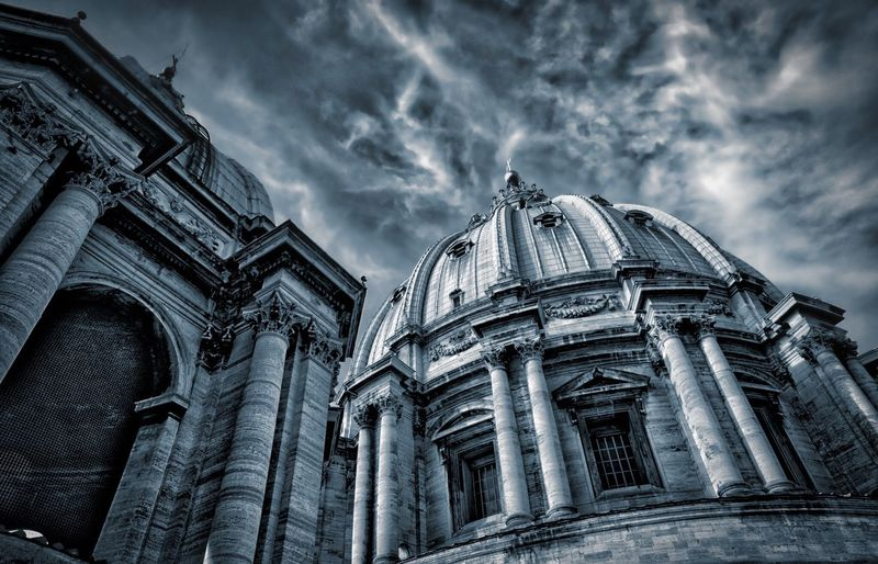 Low angle view of st peter basilica against cloudy sky