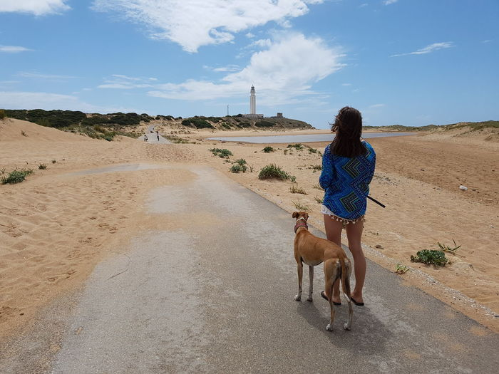 Woman with greyhound standing on road leading towards lighthouse against sky