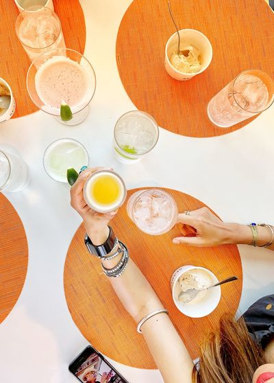Directly above shot of woman holding drink in restaurant