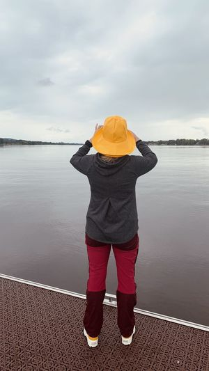 Rear view of person standing on shore against sky