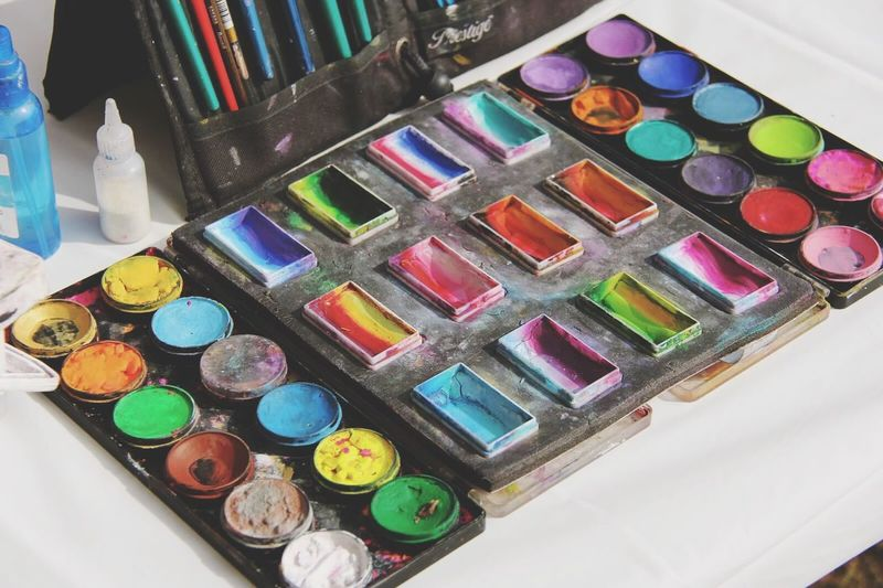 High Angle View Of Paints And Palette On Table