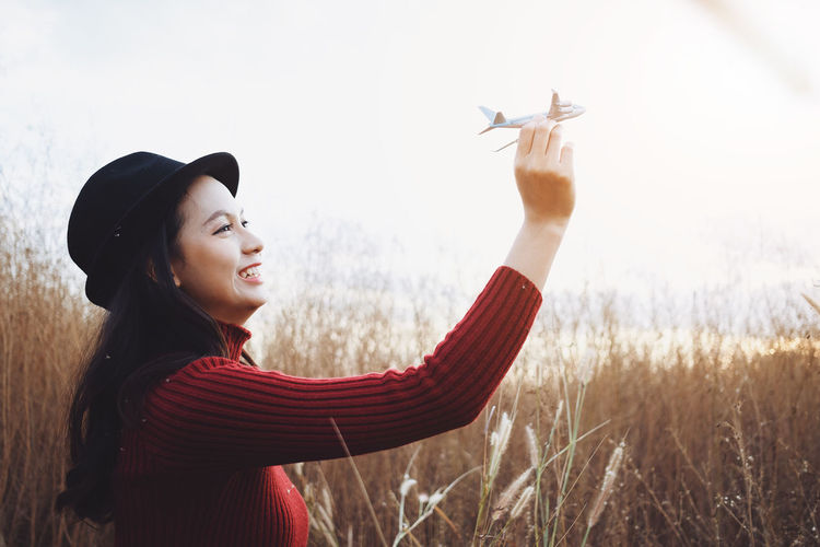 Beautiful asia woman hold plane with happy emotion in grass field Young Woman Coffee Beautiful Background Green Grass Nature Beauty Female person Girl Happy Summer Portrait Attractive Lifestyle Spring Outdoor Lady Joy Park Harmony Cup Meadow Autumn Relax Drink Relaxation Field Leisure Tea Rural Pleasure Asian  Life Fresh Morning Enjoy Heating Keep  Warm Copy Space Free Smile Cute Red Sweater Holiday Travel