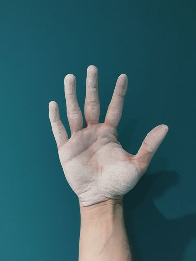 Close-up of cropped dusty hand against blue background