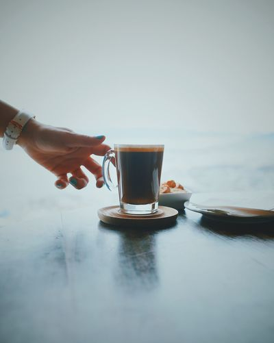 Close-up Coffee - Drink Coffee Cup Day Drink Drinking Glass Food And Drink Freshness Frothy Drink Holding Human Body Part Human Hand Indoors  One Person People Real People Refreshment Saucer Table Water