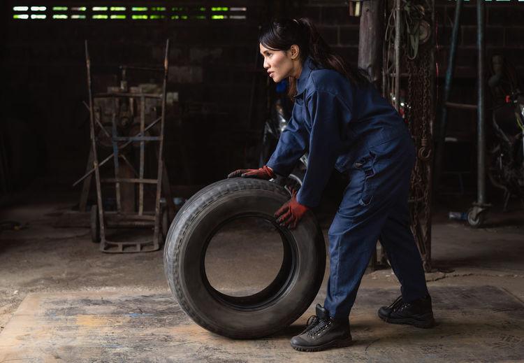 Female mechanic holding tire at garage