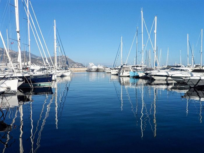 Sailboats moored in river against clear blue sky on sunny day