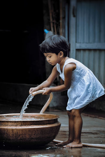 Side View Of Girl Filling Water In Container
