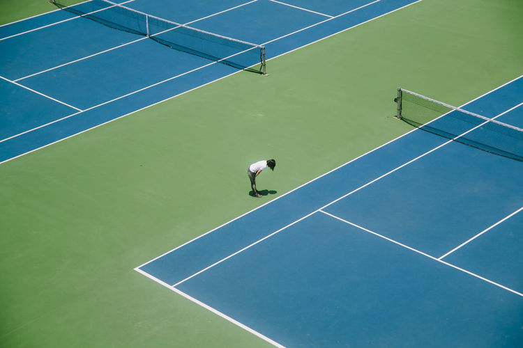 High Angle View Of Woman Standing In Tennis Court