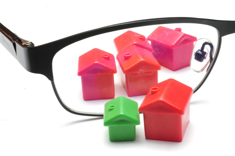 Close-Up Of Eyeglasses Amidst Model Homes Over White Background